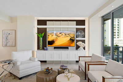 Oceanfront living room complete with custom built ins and terrace access