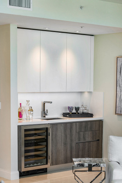 Mini wet bar adjacent to living room with chilled wine storage and custom European cabinetry